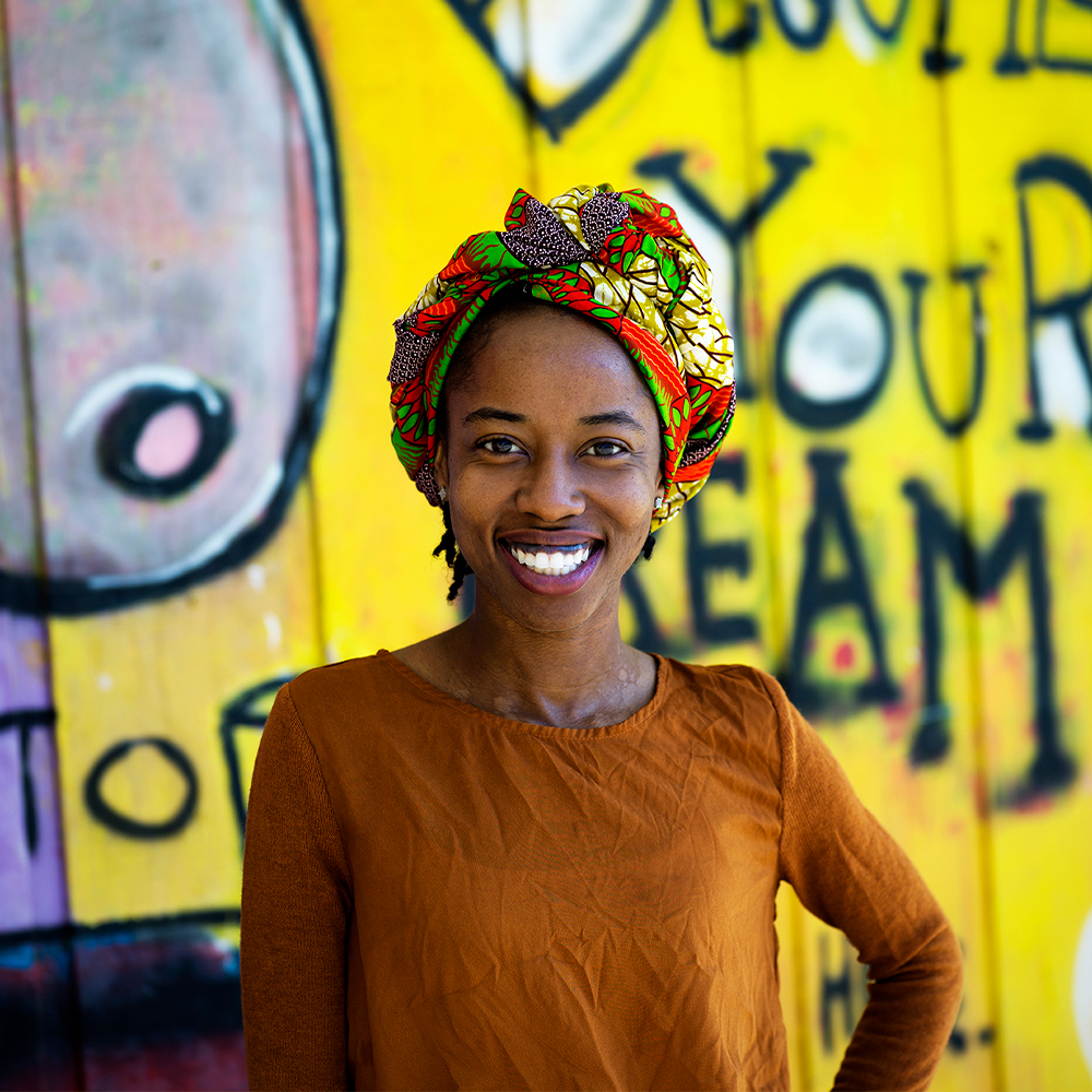 Black woman standing in front of a colorful mural, smiling