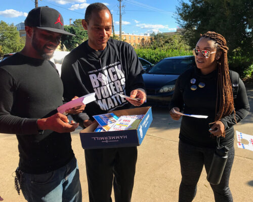 Volunteers for Black Voters Matter hand out flyers