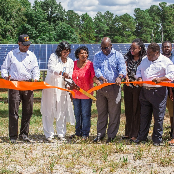 Ribbon cutting in front of solar panels