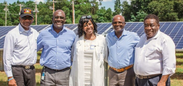 Group of black people smiling and standing in front of solar panels