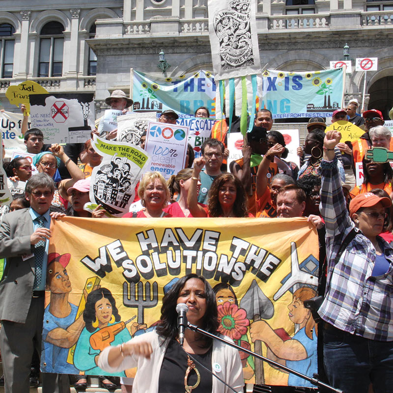 NY Renews rallying for the strongest climate bill in the country — people with signs and banners, woman speaking in front of banner that says We have the solutions